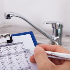 Hand Writing With Pen Water Consumption Level In Front Of Watertap